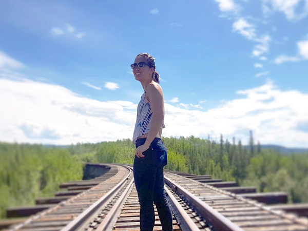 A woman stands on a train track that disappears in the distant forest. A sunny sky beats down on her.