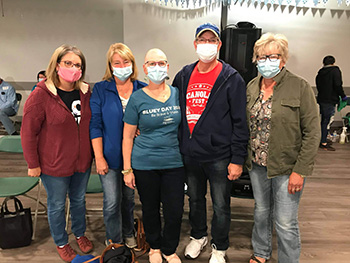 A group of five people wearing medical masks