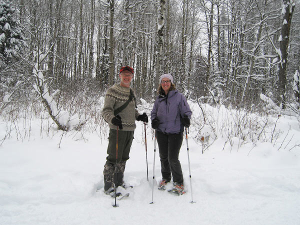 Man and woman standing in the snow with snowshoes on