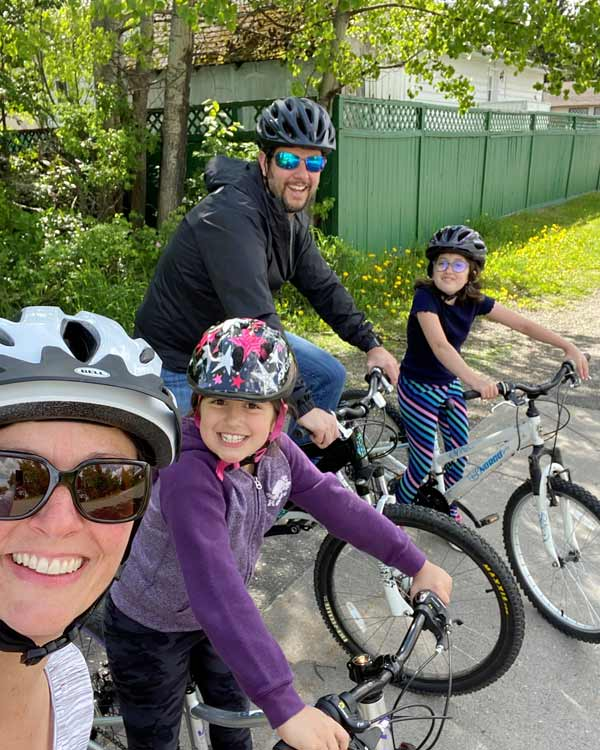A mother, father, and two daughters sit on their bikes, smiling.