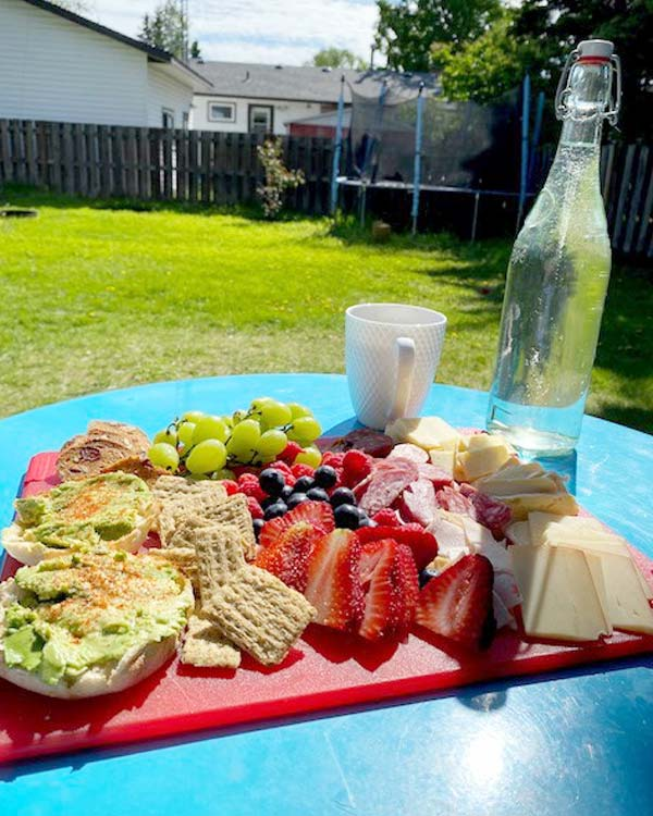 Avocado toast, fruits, meats, cheeses, and a bottle of water are on a cutting board on a backyard table.