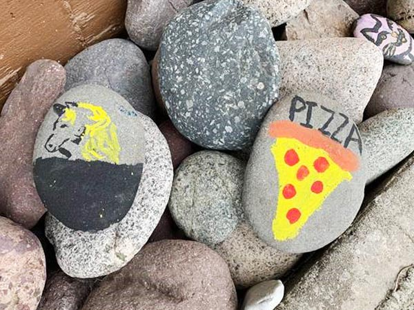 Rocks are painted, one with a cat face, another with pizza one it, and one more with a horse head.