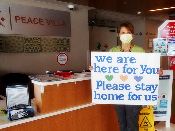 "A masked female staff member holds a sign that says, ""We are here for you. Please stay home for us."""