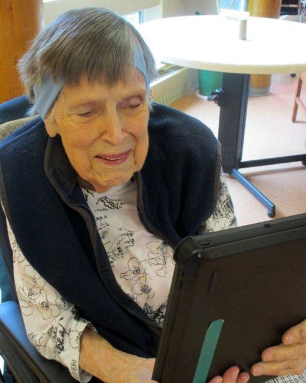 An elderly woman in a wheel chair smiles as she operates an iPad.