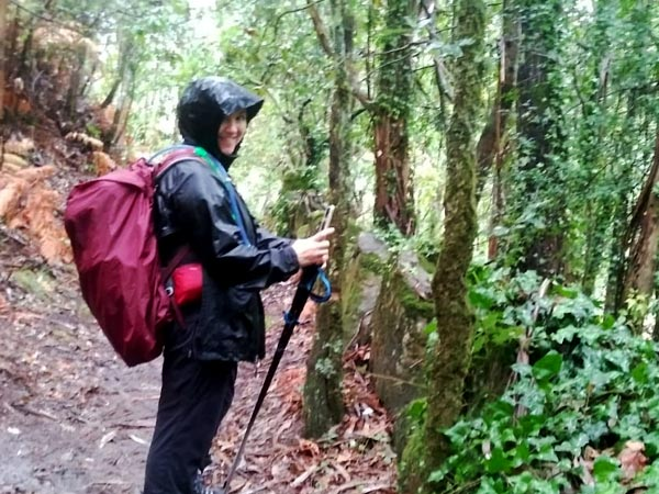 A woman in rain gear hikes in wet weather and smiles into the camera.