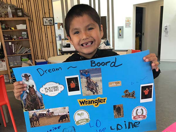 A young boy holds up a poster board, titled Dream Board, with magazine cut outs of horses and cowboys.