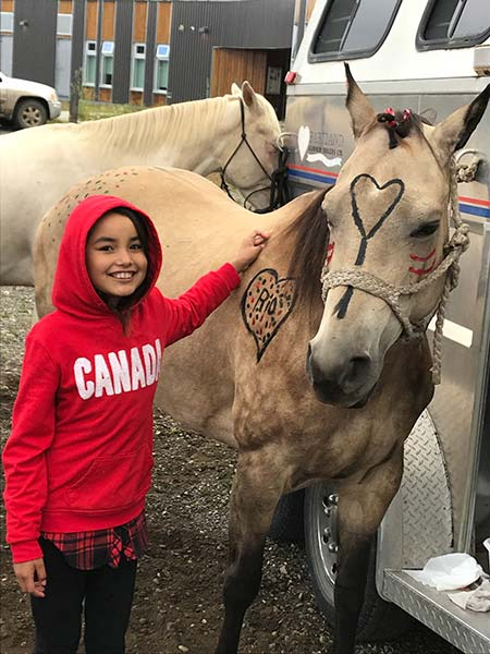 A young girl in a red hoodie stands next to a horse that is decorated with paint.