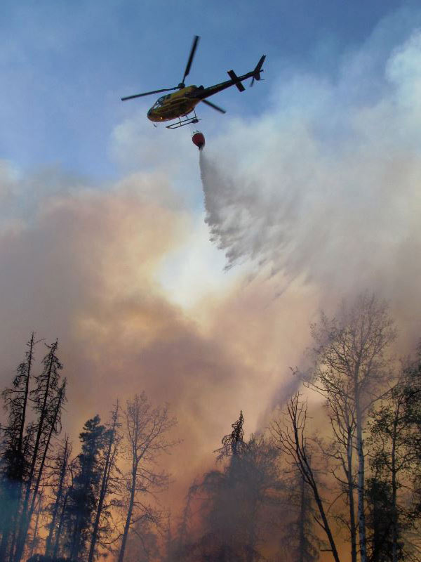 A helicopter delivering water for aerial firefighting near Chetwynd in 2017.