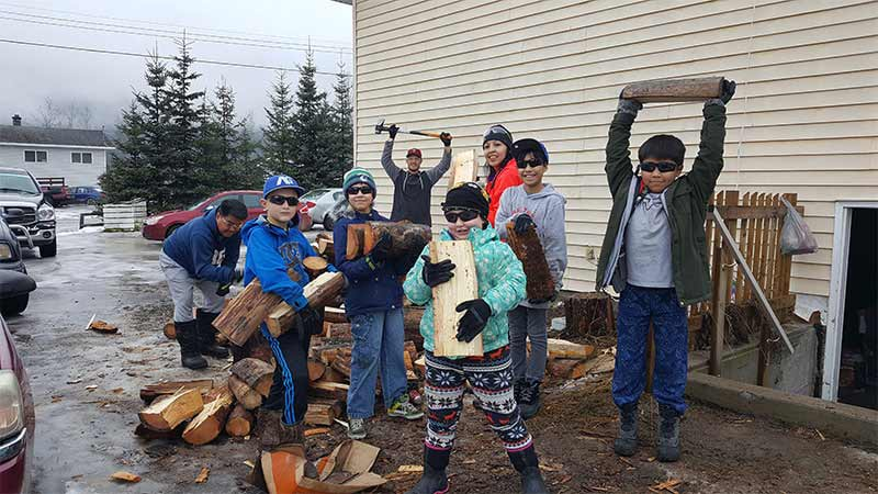 Kids helping elders cutting wood beside a house during winter.