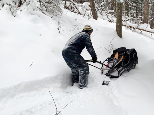 A person cuts a trail out of the snow using a trail making machine.