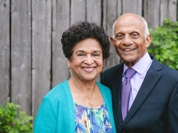 An senior man and woman stands in front of a fence smiling.