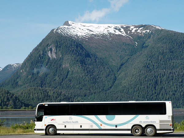 A charter bus is parked in front of a river and mountain range.