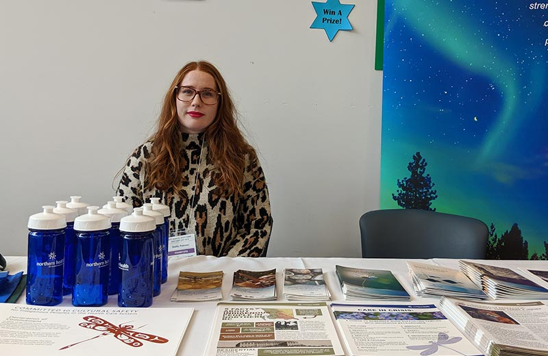 A woman sits behind a table with Indigenous Health pamphlets on it.