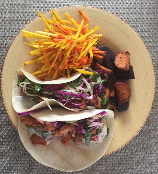 2 tacos on a plate with vegetables and fish.