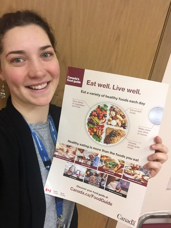 Smiling woman with brown hair and silver earrings hold a copy of Canada's food guide.
