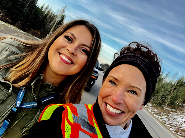 Two smiling women pose for a selfie outside on a road lined with snow and trees.
