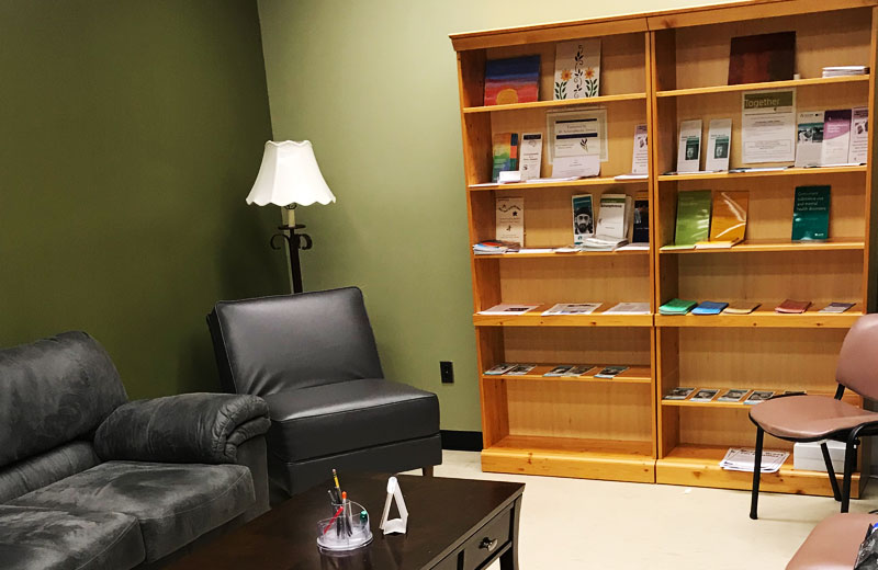 A chair and couch sit next to a book shelf with pamphlets on it.