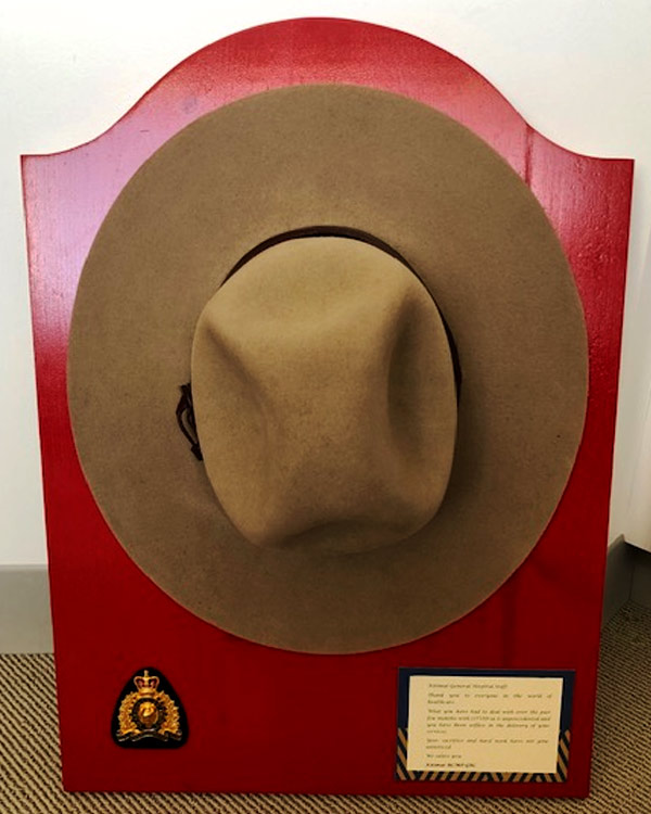 A plague on red wood features a mounted police officer's hat and badge, and an inscription.
