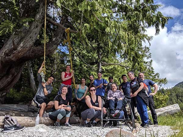 A group of people on a beach at the edge of large trees, with a woman sitting in the Trail Rider equipment.