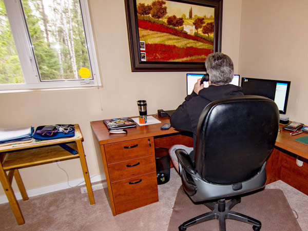 A man faces his desk and two monitors in his home office. To his right, a coffee and Rubiks cube sit under a window. Outside is a forest.