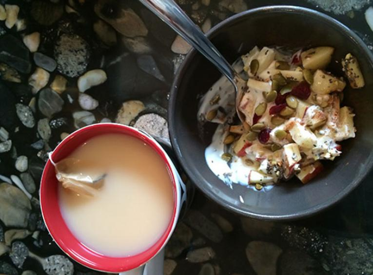 Bowl of yogurt with cup of tea.