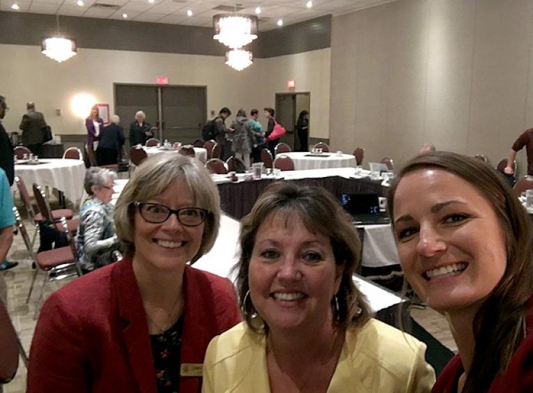 From left to right, Cathy Ulrich, NH CEO; Colleen Nyce, NH Board Chair; and Julianne Kucheran, Community Consultant, Urban Matters smile into the camera as a meeting breaks behind them.