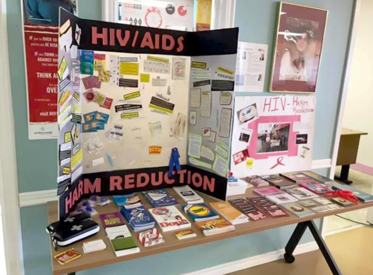A table of HIV Awareness materials is pictured.