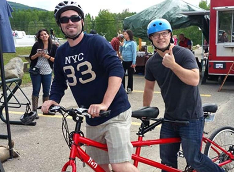 Two men on tandem bike.