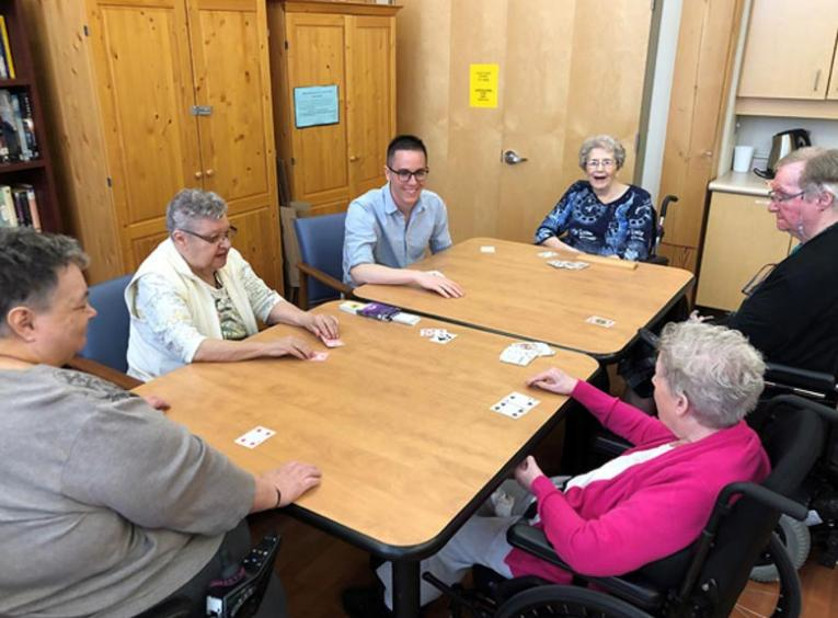 Zach, a young man, plays cards with five seniors.