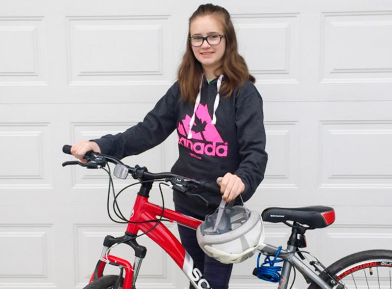 A young girl, wearing a black and pink hoodie, poses with her red bike and helmet.
