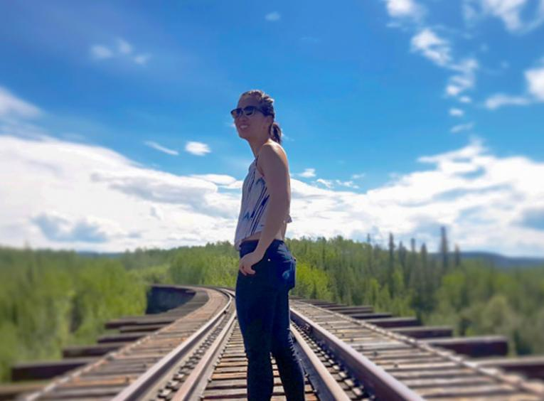 Melinda stands on a train track that disappears in the distant forest. A sunny sky beats down on her.