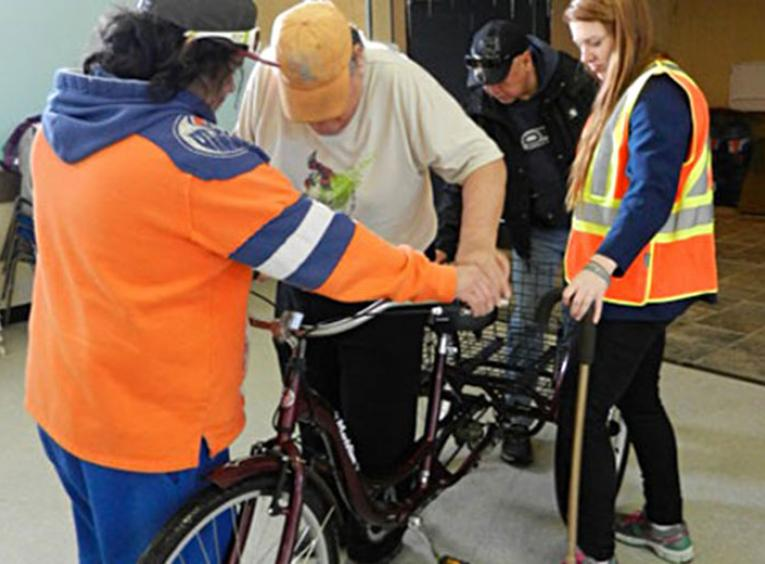 Staff supporting elder on a bicycle.