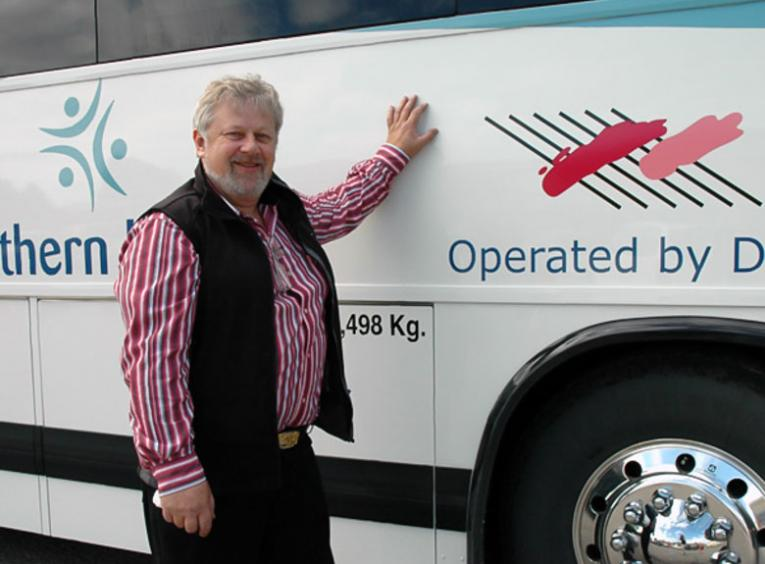 A man leans on an NH Connections bus.