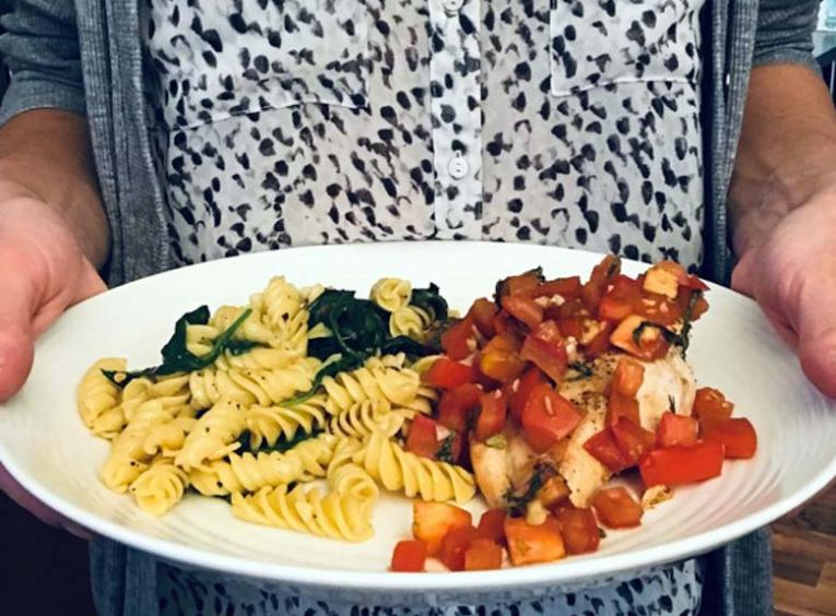 A person holds a white plate of food. On the left of the plate is pasta noodles with spinach, on the right is a chicken breast covered in chunks of tomato.