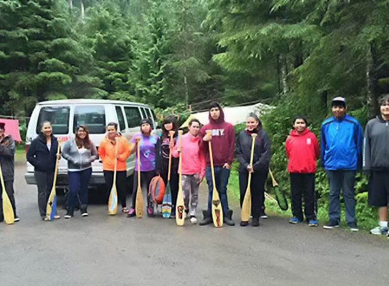 Youth group on forest roadside with paddles.