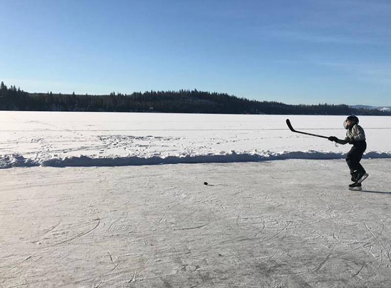 boy playing hockey on frozen lake.