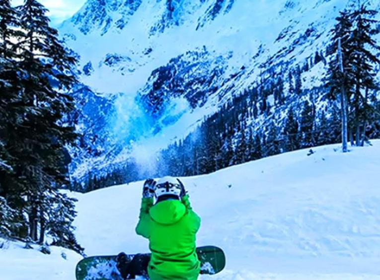 snowboarder sitting down on a ski hill