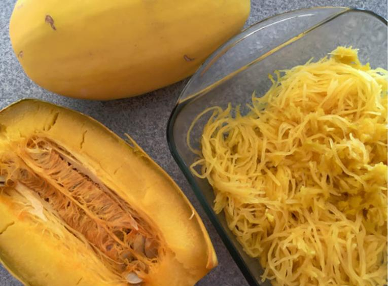 An opened spaghetti squash and the inside 'noodles' in a dish.
