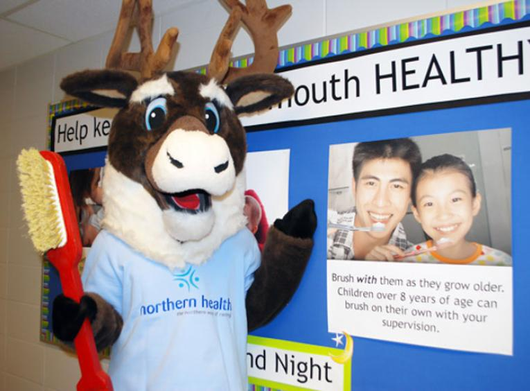 Spirit the Cariboo holding a toothbrush with a poster that shows how adults should brush with children.