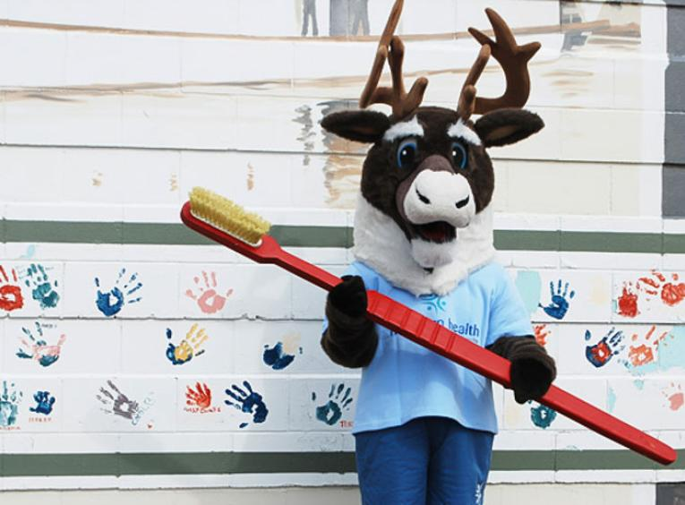 Spirit the Cariboo holding a large toothbrush, standing against a mural of handprints.