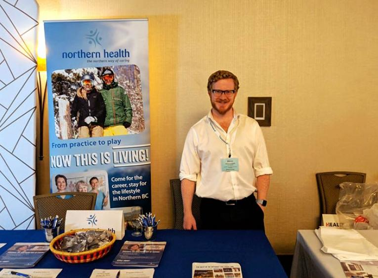 A man stands smiling in the Northern Health recruitment booth