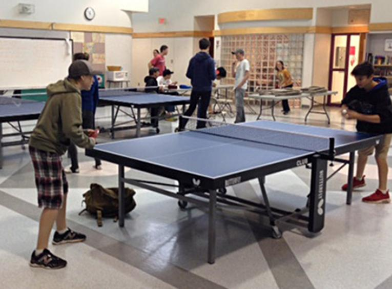 Students playing table tennis in a gym hall.