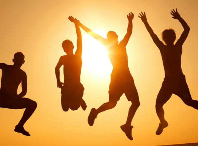Silhouette of four people jumping together against setting sun behind