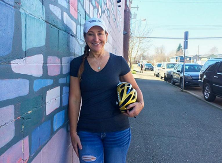 Woman standing in street holding cycling helmet.