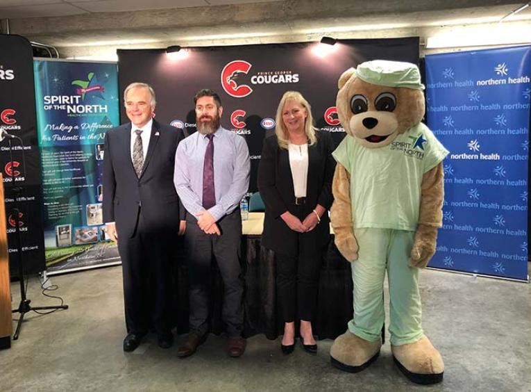 A man in a suit, a man in a tie, a woman in a suit, and a giant teddy bear mascot lined up.