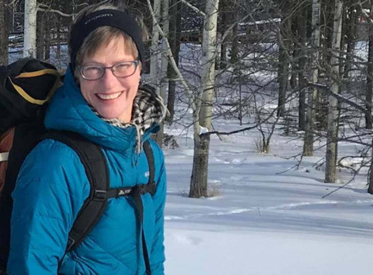 Woman on a trail hiking in snow during winter.