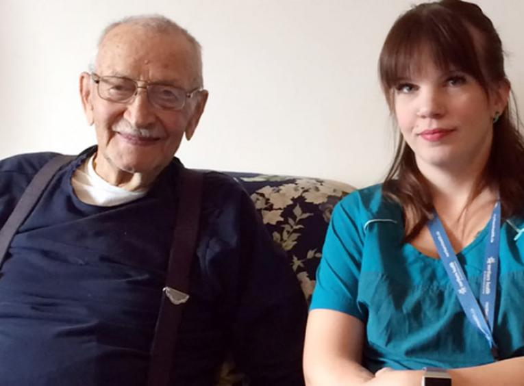An elderly man and a young woman sit on a couch.