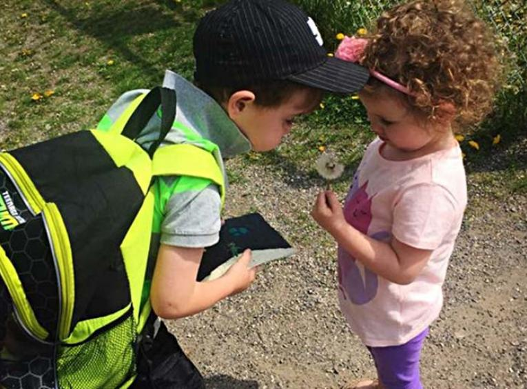 Young boy with backpack and ball cap on interacting with another young child.