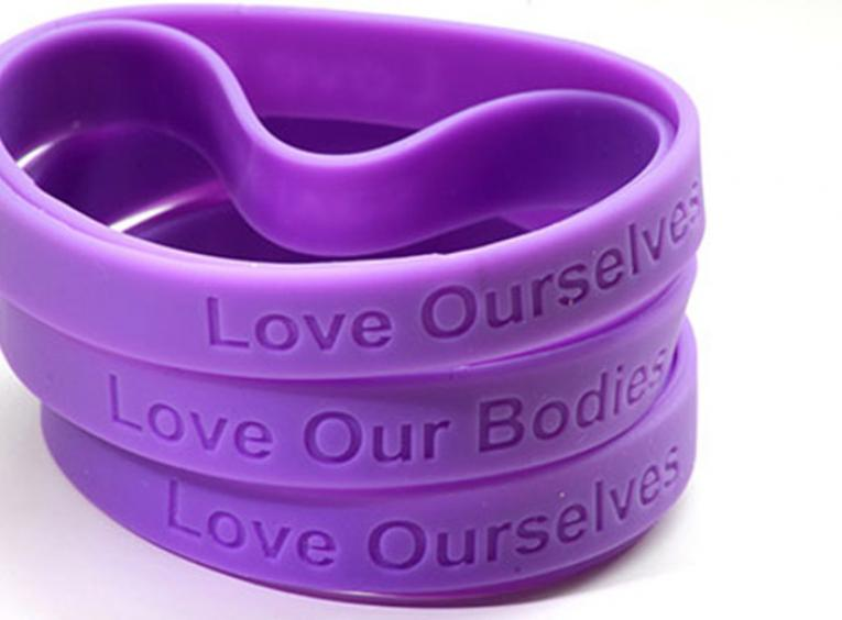 Wristbands stating Love Ourselves and Love Our Bodies.