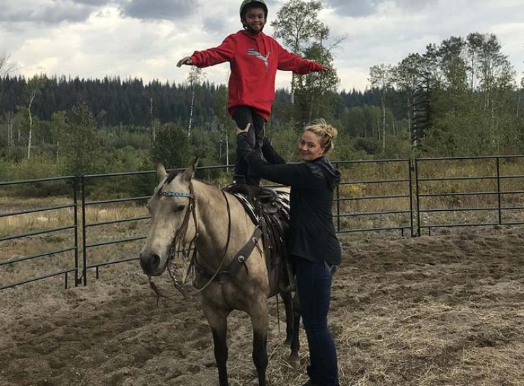 A woman poses, holding the legs of a young boy who is standing on top of a saddled horse in a field.